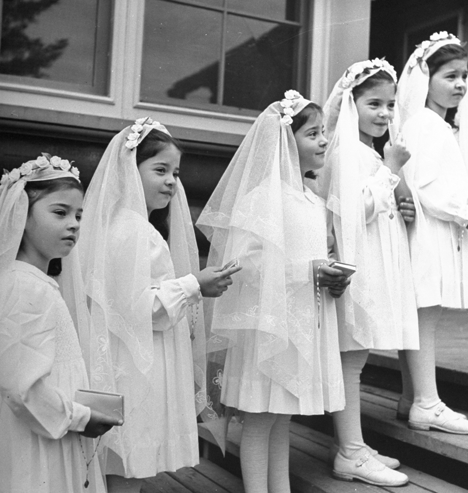 "A view of the ""Dionne Quintuplets"" posed in their confirmation dresses on day of their first Holy Communion, 1940."