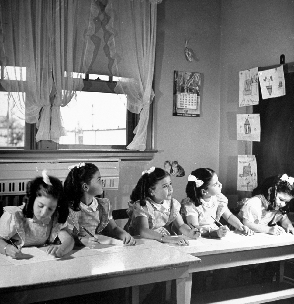 Writing lesson in nursery schoolroom is the Quins' first exercise in the discipline of formal education. Above (left to right): Cecile, Annette, Emilie, Marie and Yvonne study a word on the blackboard, then duck their heads to print it out.
