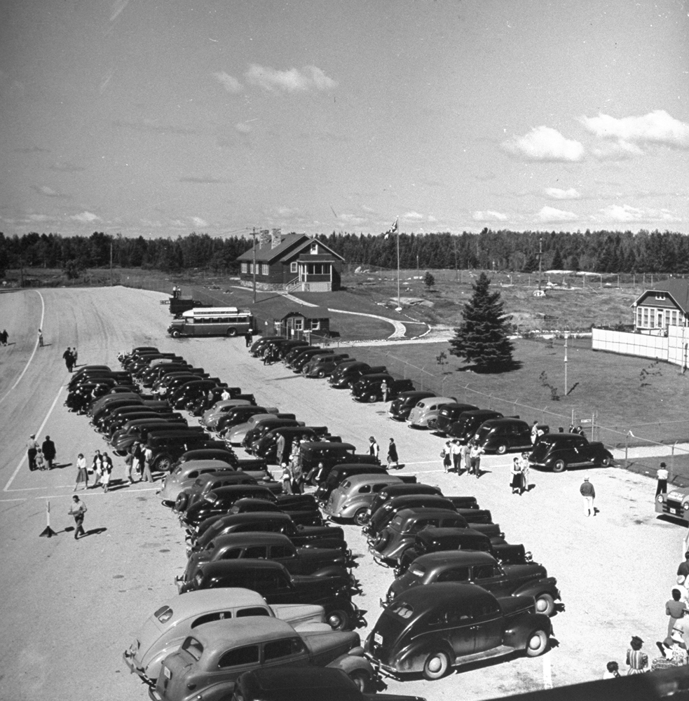 Tourists pulling up to visit the home of the Dionne Quintuplets, Canada, 1940.