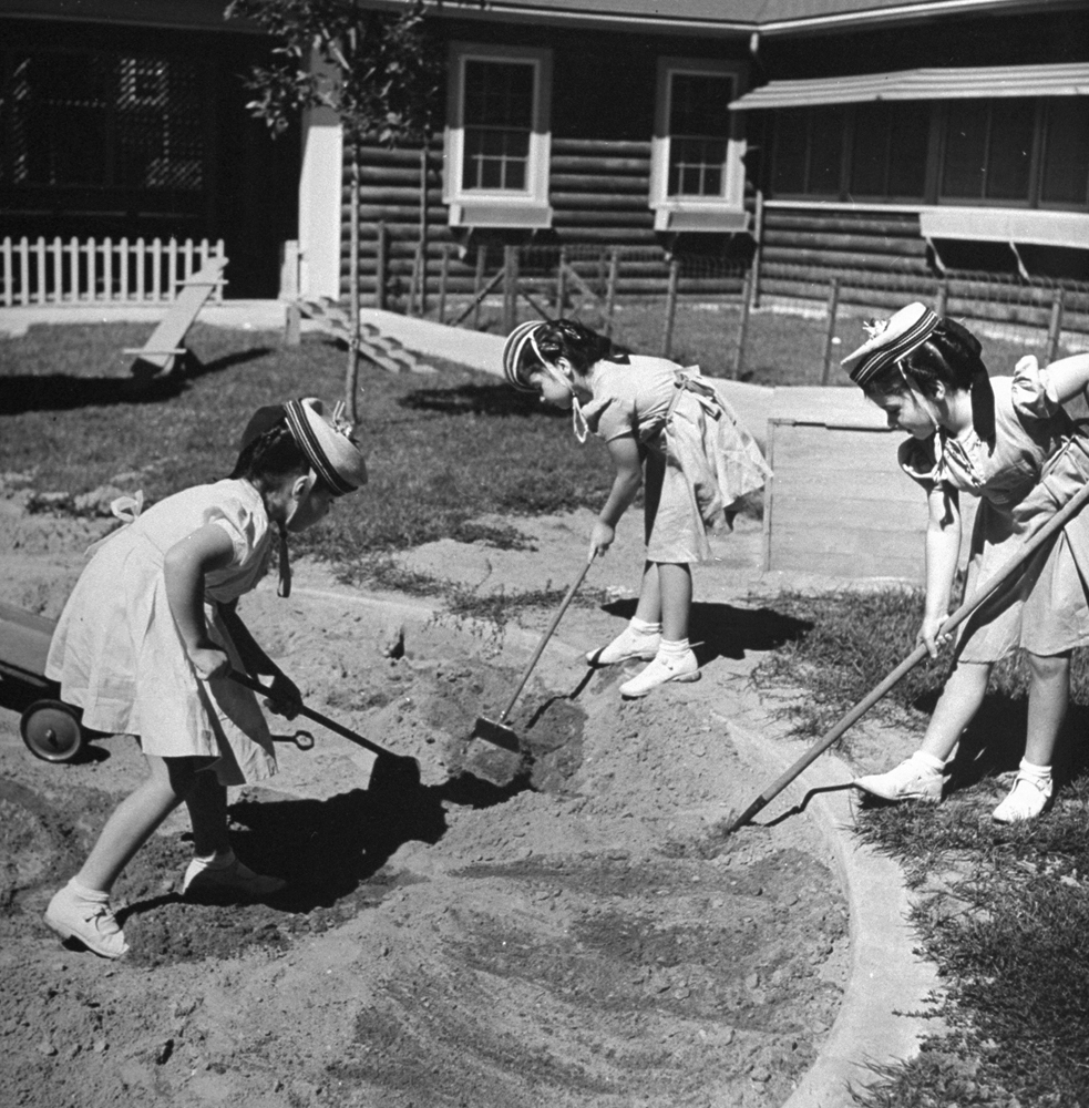 Three of the Dionne Quintuplets playing in the yard of their home/compound, 1940.