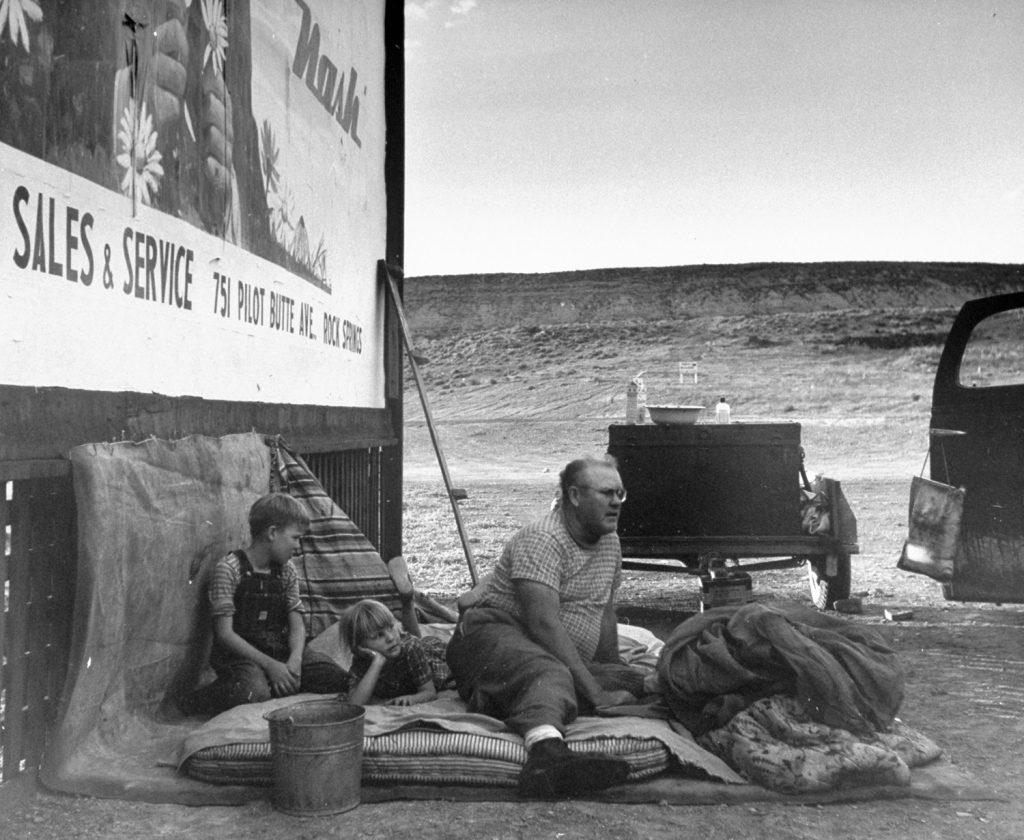 Family sleeping outside by a billboard alongside Route 30, Wyoming, 1948.