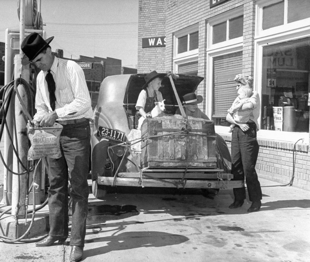 Driver filling a water bag at a gas station alongside Route 30, 1948.