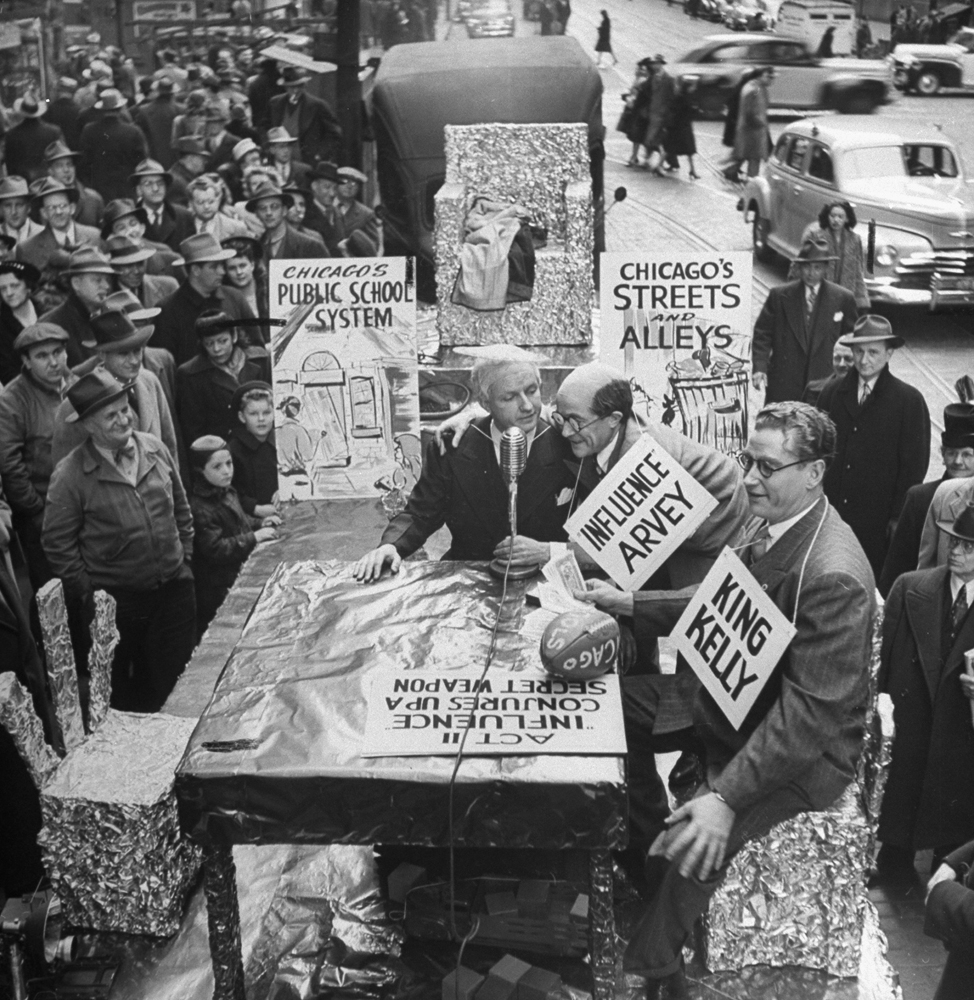 People gathering on the street to watch a satire of political officials, Chicago, 1947.