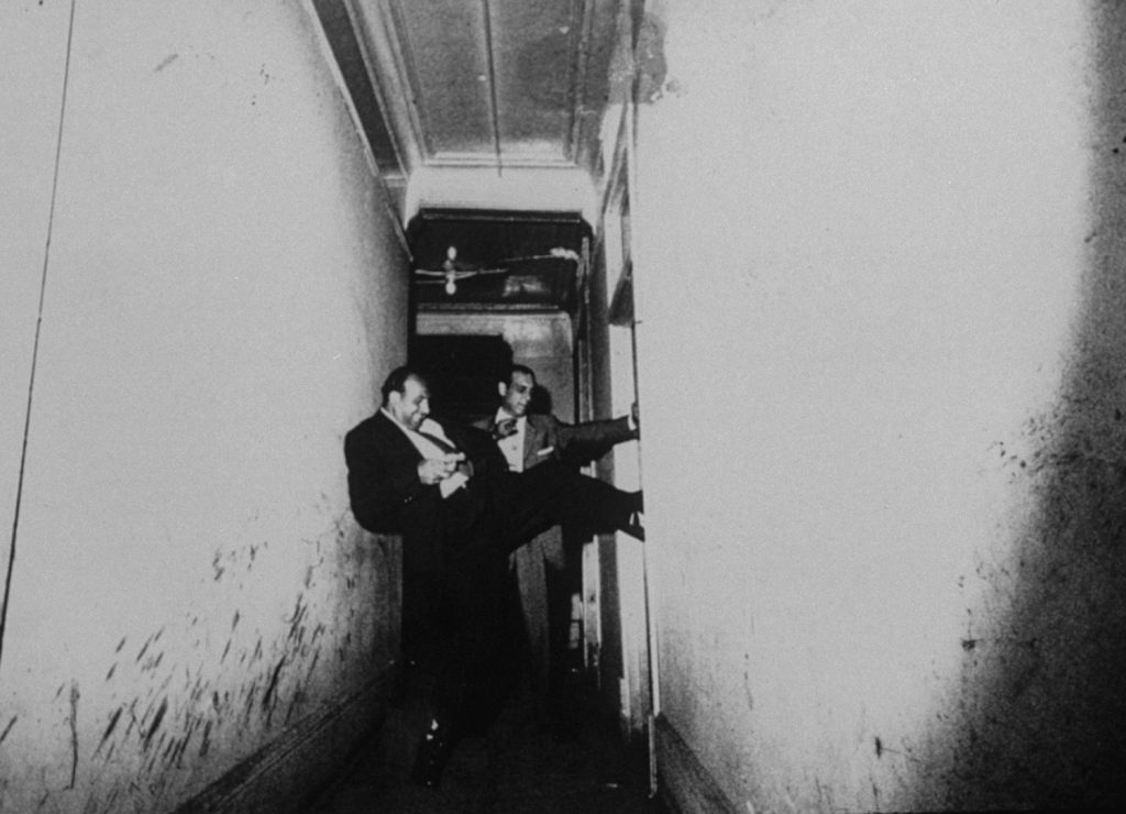 Chicago detectives force their way into an apartment, 1957.