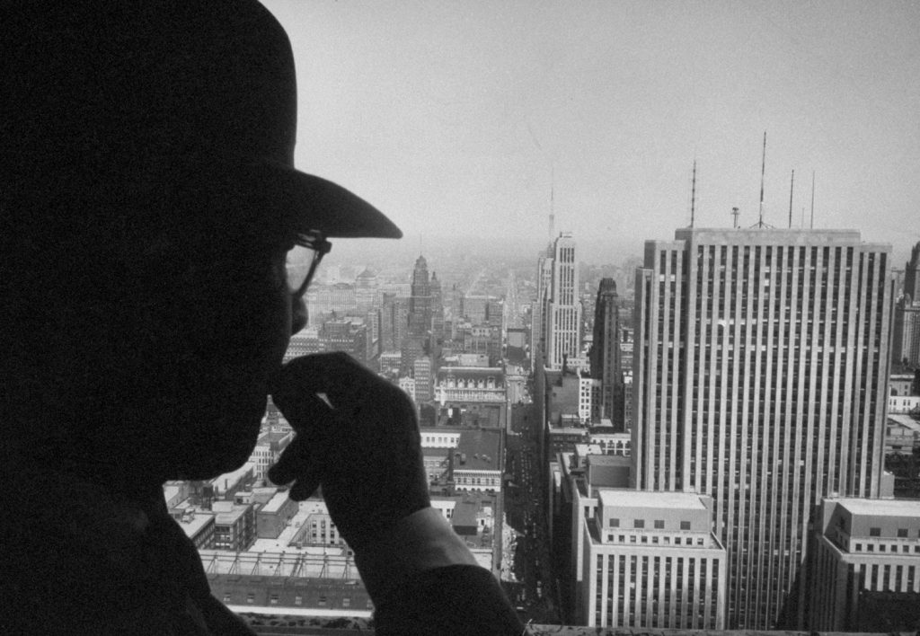 Poet Carl Sandburg looks out a window in the Chicago Board of Trade Building, 1957.