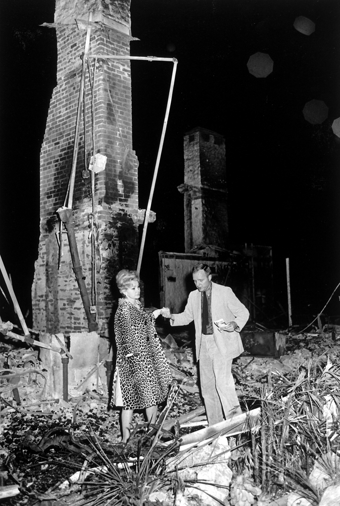 LIFE magazine editor Richard Stolley helps Zsa Zsa Gabor through the remains of her Bel Air, Calif., home, destroyed by fire in November 1961.