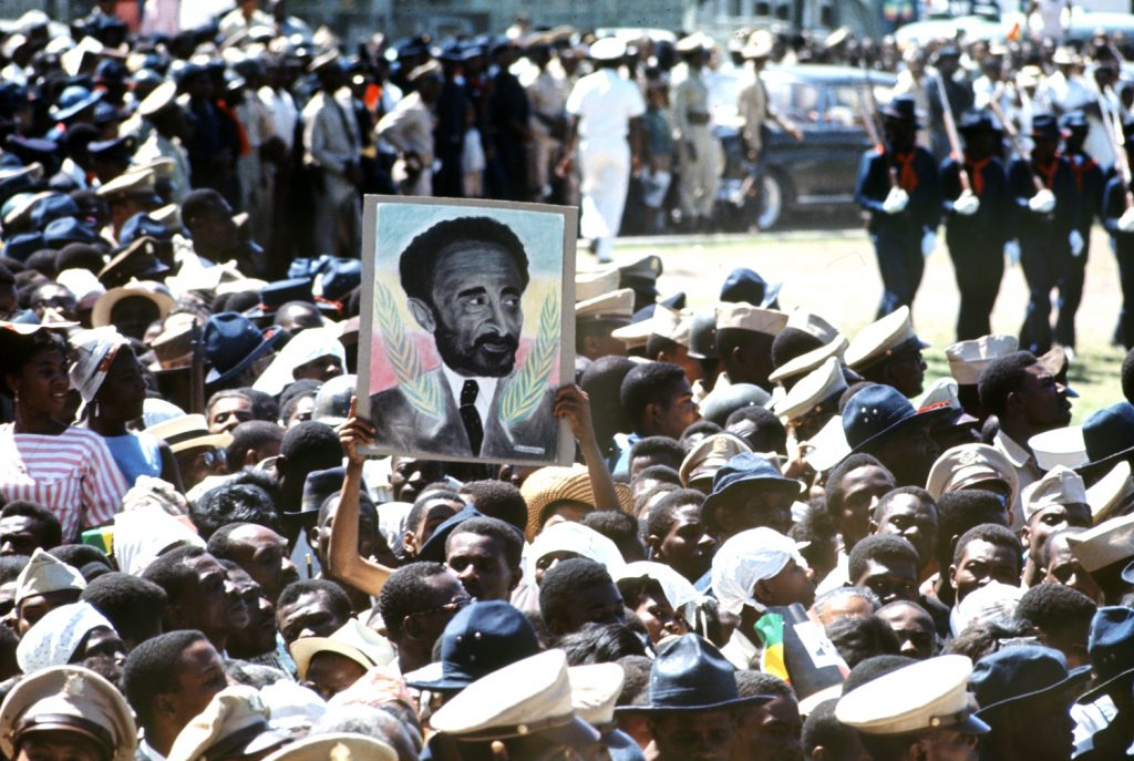 Portrait of Haile Selassie I held aloft in a crowd, Jamaica, 1966.