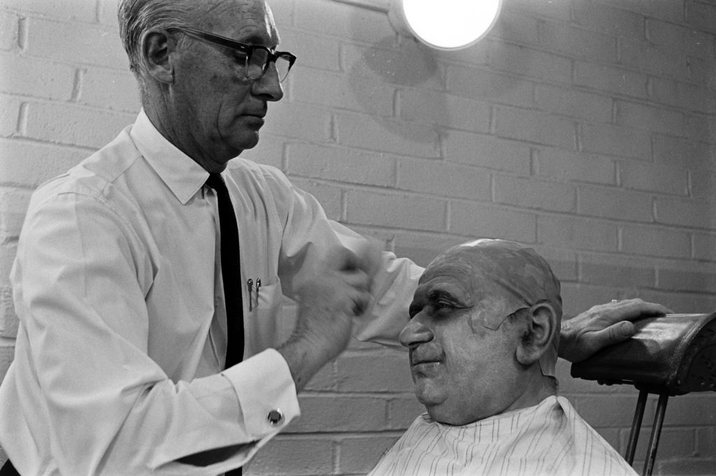 A makeup artist with actor (possibly Jackie Coogan) auditioning for the role of Uncle Fester, 1964.