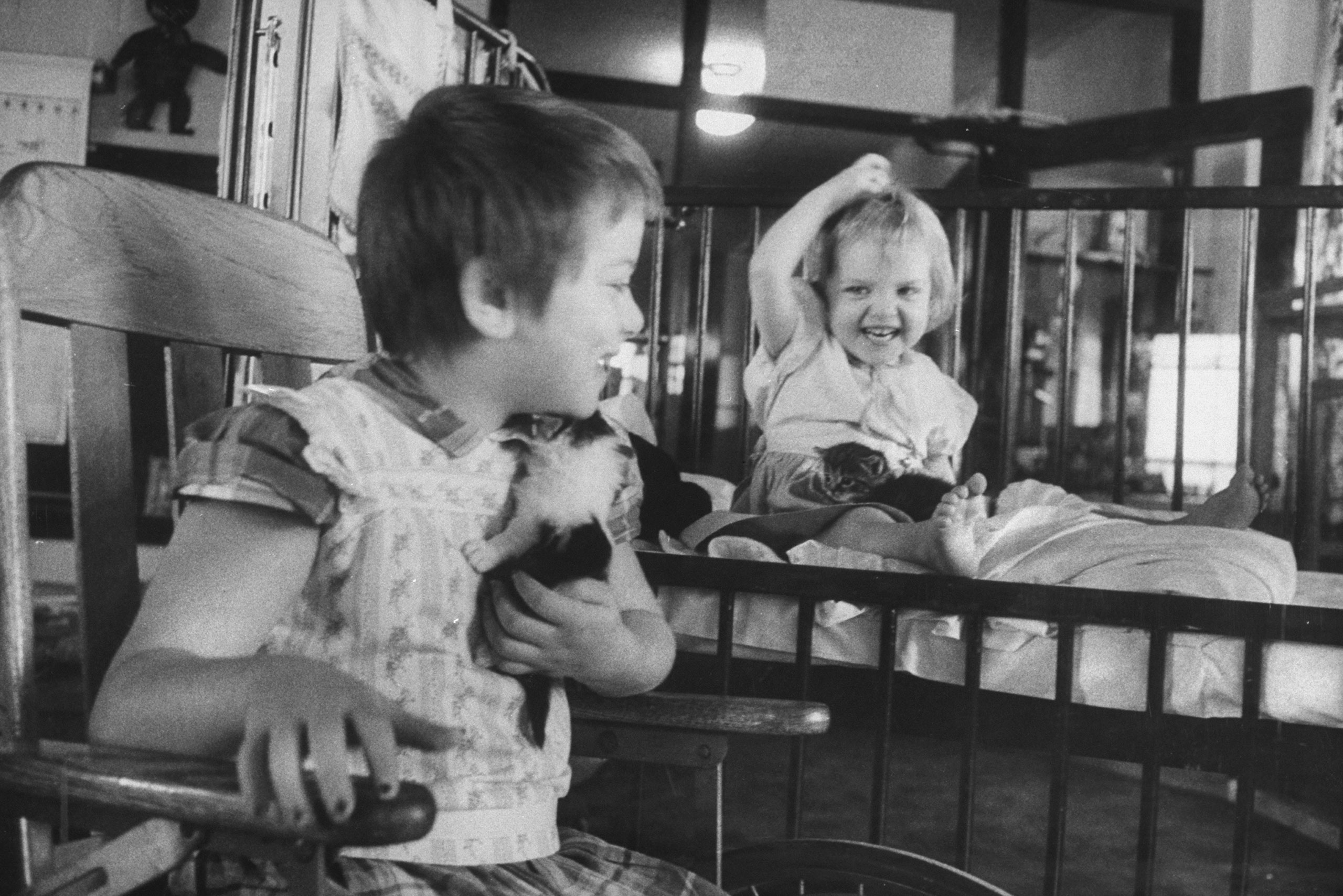 Two children play with kittens at the University of Michigan's hospital at Ann Arbor, 1956.
