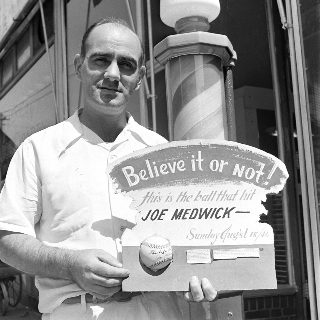 Jack Kaufman outside his barber shop on Rogers Avenue in Brooklyn in 1946, holding a signed baseball that once beaned future Hall of Famer Joe Medwick.