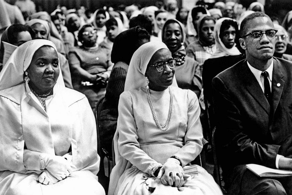 Daughter and wife of Elijah Muhammad with Malcolm X, Chicago, 1961.