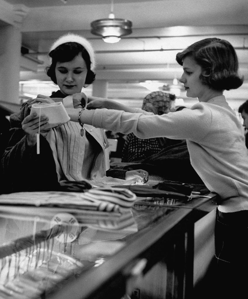 Attractive young sales girl holding blouse up to customer in store, as customer is looking at other things to buy.