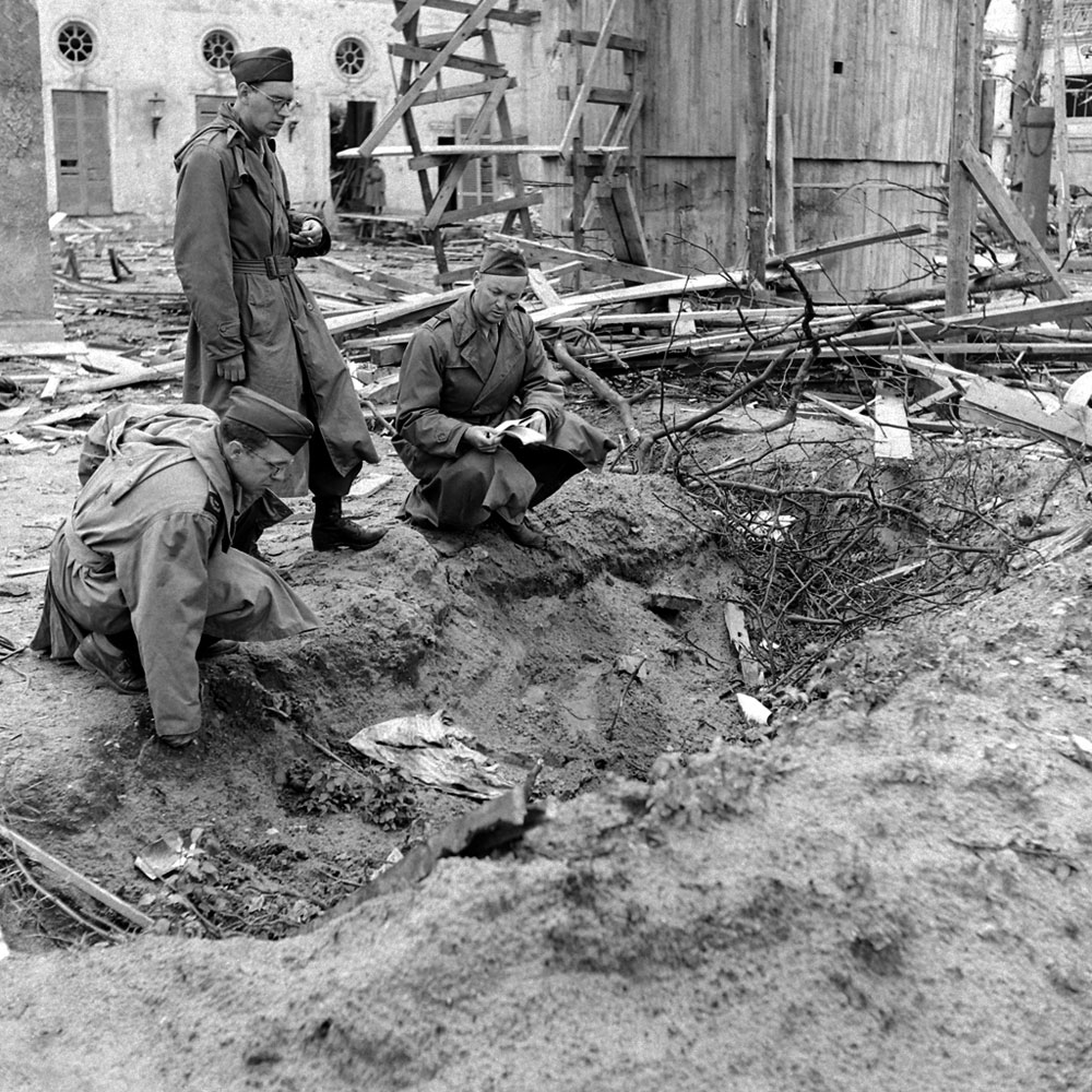 LIFE correspondent Percy Knauth, left, sifts through debris in the shallow trench in the garden of the Reich Chancellery where, Knauth was told, the bodies of Hitler and Eva Braun were burned after their suicides.