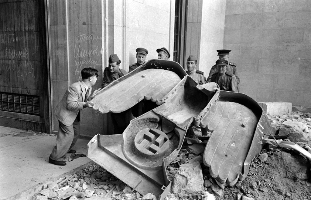 Russian soldiers and a civilian struggle to move a large bronze Nazi Party eagle that once loomed over a doorway of the Reich Chancellery, Berlin, 1945.