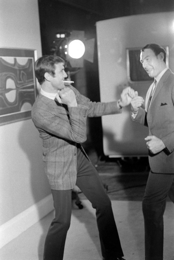 George Lazenby goofs off behind the scenes of his screen test, boxing with an unidentified man, 1967.