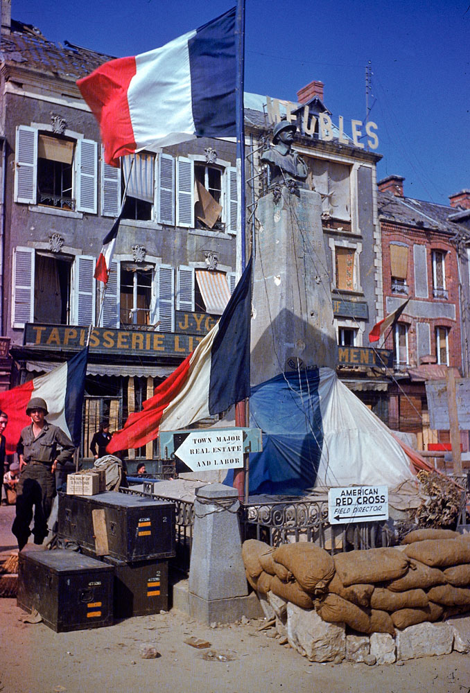 American troops stand beside a World War 1 monument bedecked with French flags after the town (exact location unknown) was liberated from German occupying forces, summer 1944.