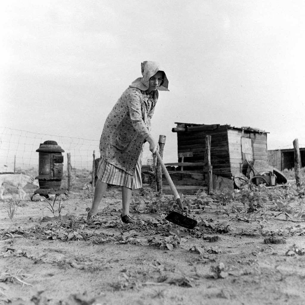 Farmer John Barnett's wife, Venus, works in her vegetable garden after a second planting, Oklahoma, 1942. A windstorm earlier in the year blew the first seedlings away.