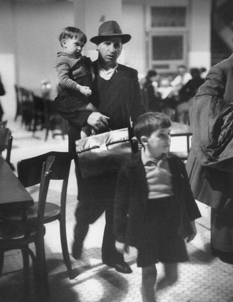 """Antonio Magnani copes with his children and fat briefcase holding his entry papers."" Ellis Island, 1950."
