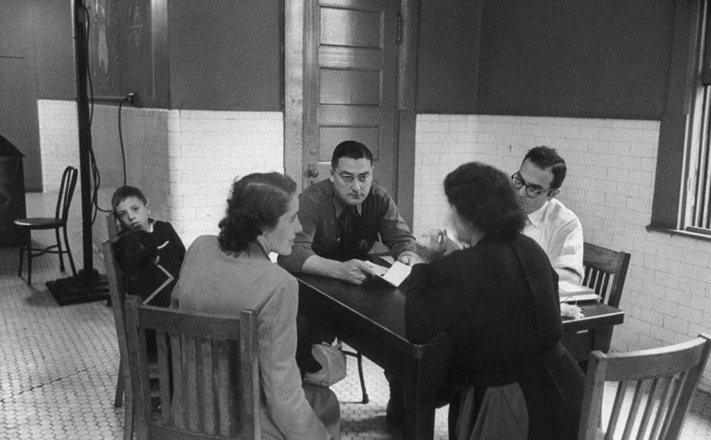 """Maria Nadalin of Italy, seated at left of the table, is worked on by an inspector-stenographer-interpreter team ..."""