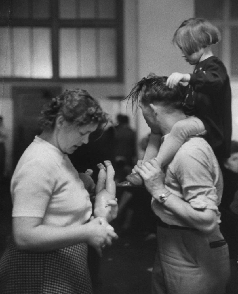 """Exhausted parents in recreation hall try to keep their child amused and quiet. Most of them will put up with endless piggyback riding, hair-pulling -- anything -- to get relief from the bewildered crying."""