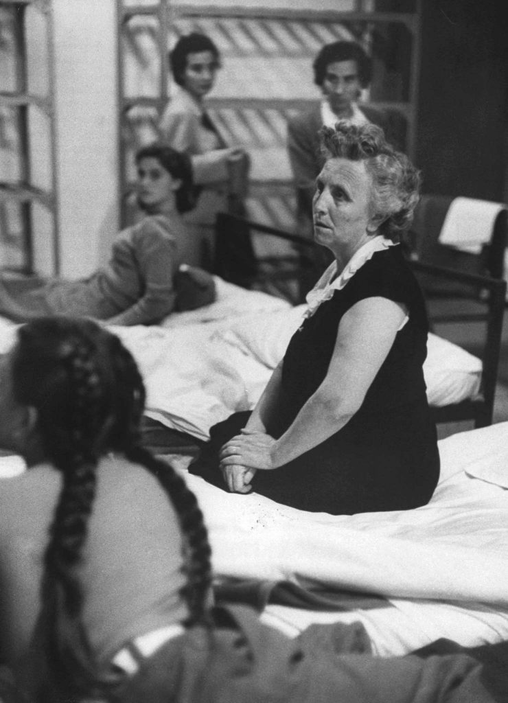 """In women's dormitory, separated from husbands, wives sit silently on their beds. At right is Maria Palmerini of Italy, here for a six-month visit. She receives same treatment as those who will stay."""