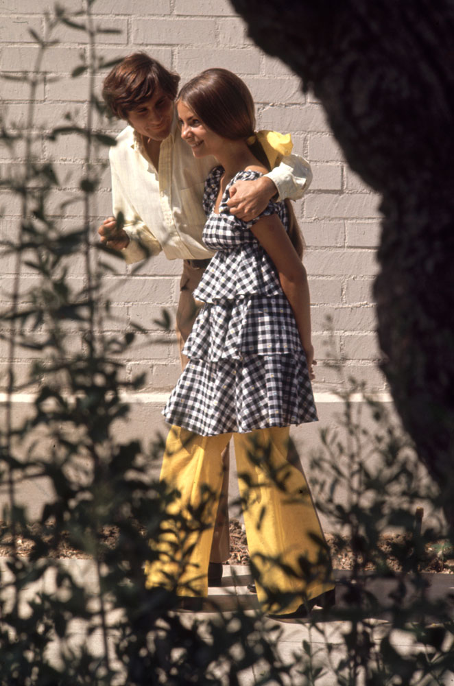 Beverly Hills High School student Erica Farber, wearing a checkered and tiered outfit, walks with a boy, 1969.