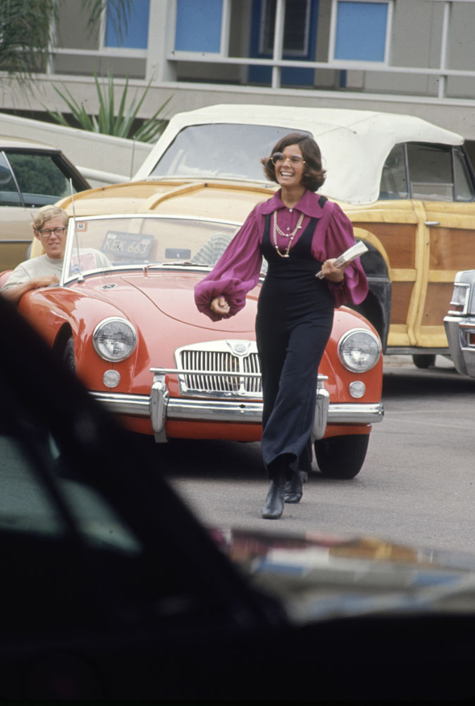 High schooler Lenore Reday stops traffic while wearing a bell-bottomed jump suit in Newport Beach, Calif., 1969.
