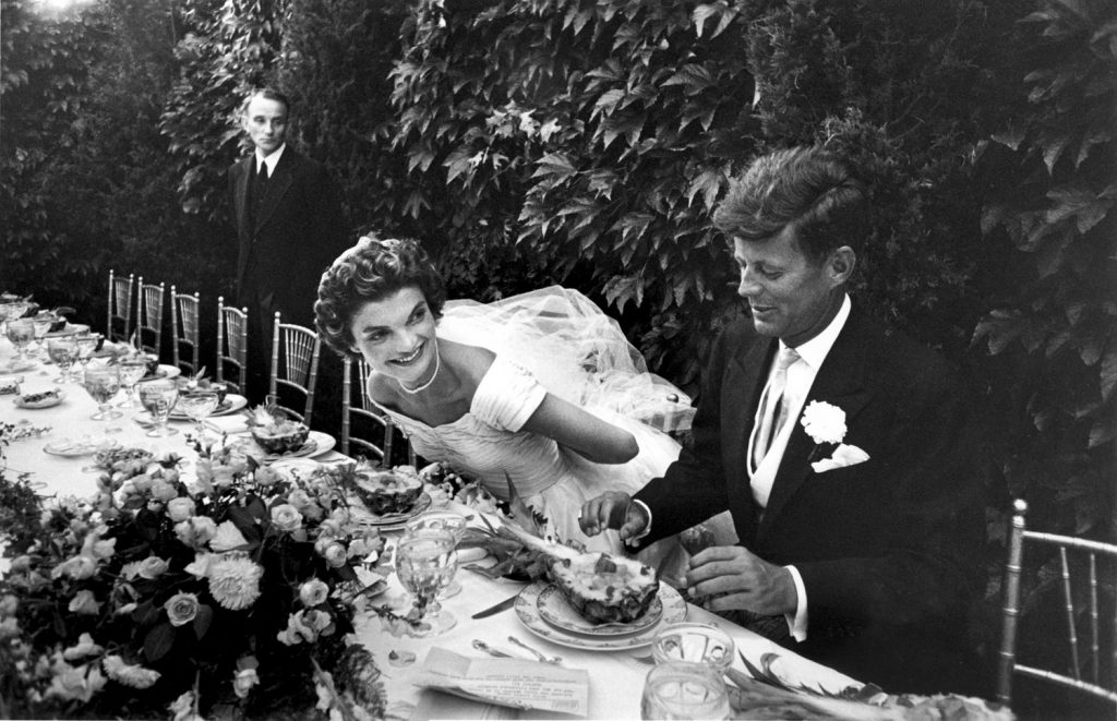 """Bride and bridegroom finally sit down to lunch after the long, wearying ordeal of the receiving line. Jacqueline, whose wedding dress contained 50 yards of material, adjusts veil while her senator husband starts right in on fruit cup."""""""
