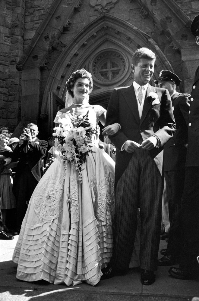 """""""Jacqueline Bouvier in gorgeous Battenburg wedding dress with her husband Sen. John Kennedy as they stand in front of church after wedding ceremony."""""""