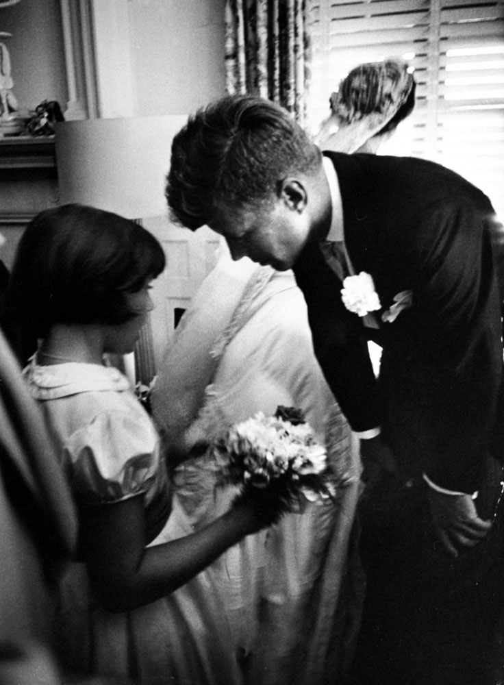 """""""Flower girl Janet Auchincloss, half sister of bride, talks to Kennedy while bride looks out window at guests waiting to go through receiving line."""""""