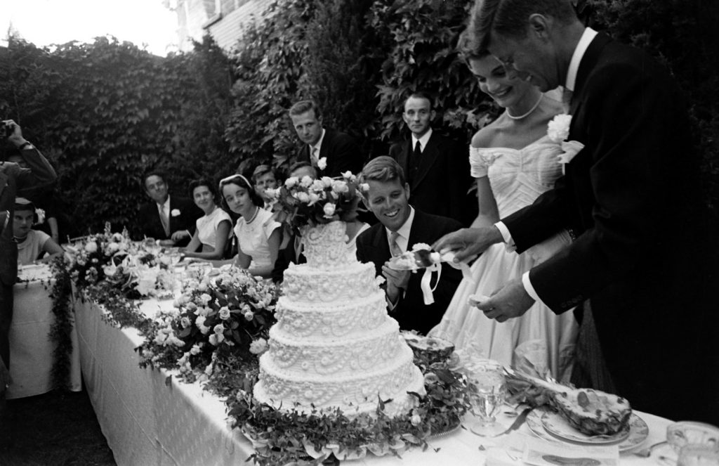 Guests, including Robert Kennedy, watch as newly married John and Jackie Kennedy cut their wedding cake, Newport, R.I., Sept. 12, 1953.