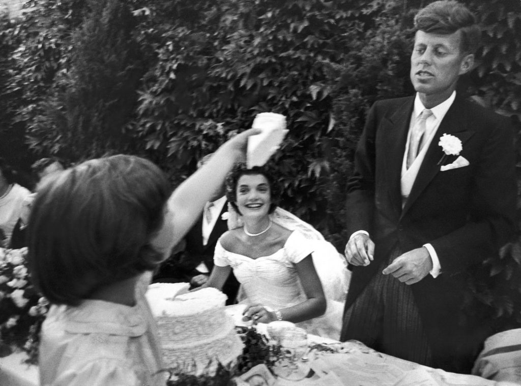"""""""Slice of wedding cake is offered bridegroom by flower girl Janet at the luncheon. Kennedy had already had some cake so did not want any more."""""""