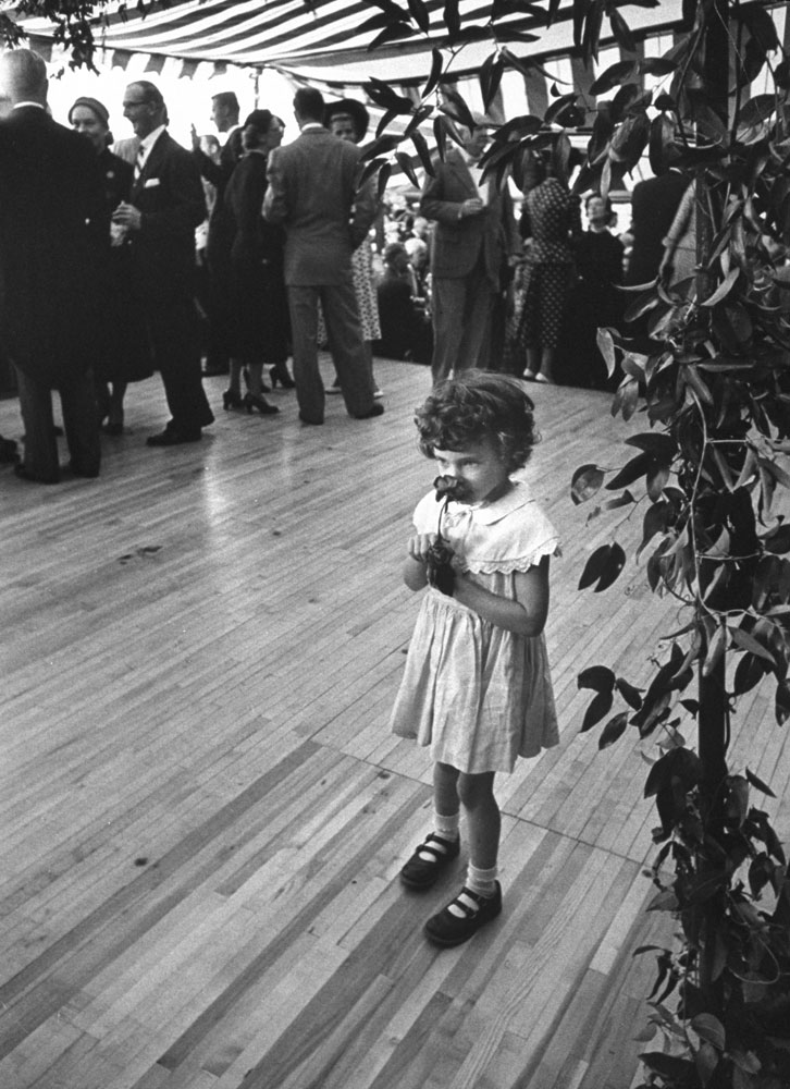 A girl with a flower at John and Jacqueline Kennedy's wedding reception, Newport, R.I., Sept. 12, 1953.