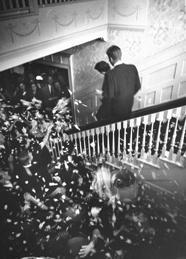 """""""Off for honeymoon in Acapulco, Mexico, the bride and bridegroom leave the wedding reception amid a shower of rose-petal confetti and rice."""""""