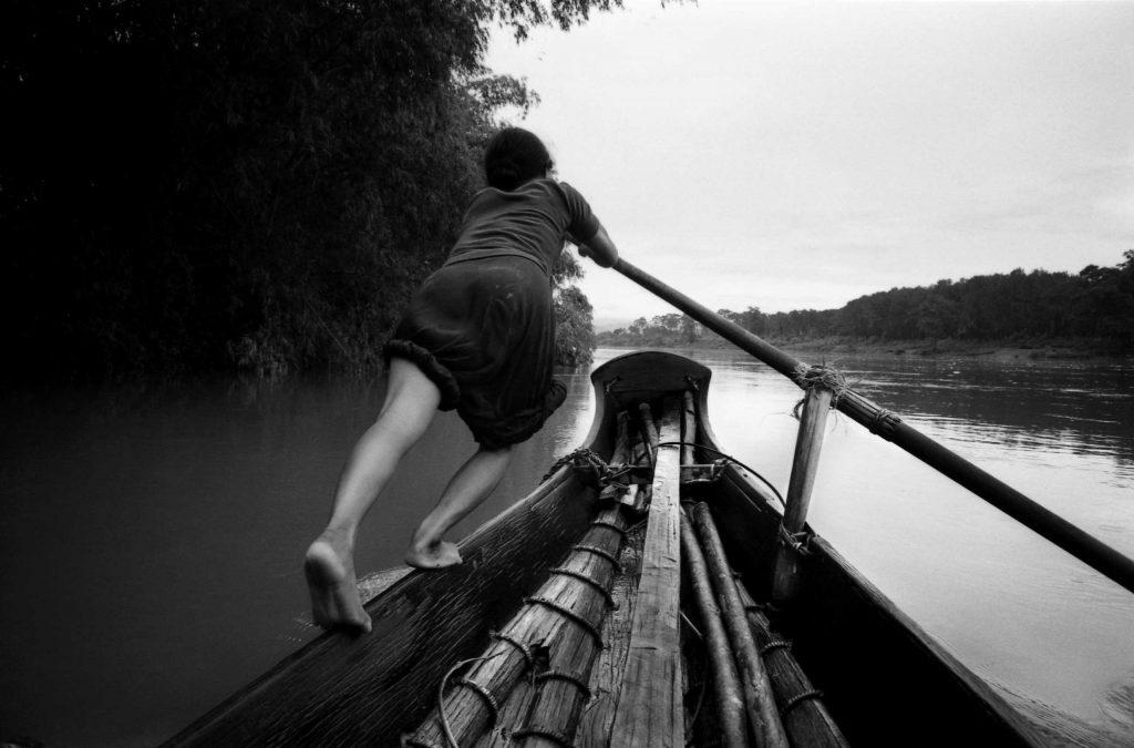 A boat girl rows a sampan across the Perfume River, Vietnam, 1961.