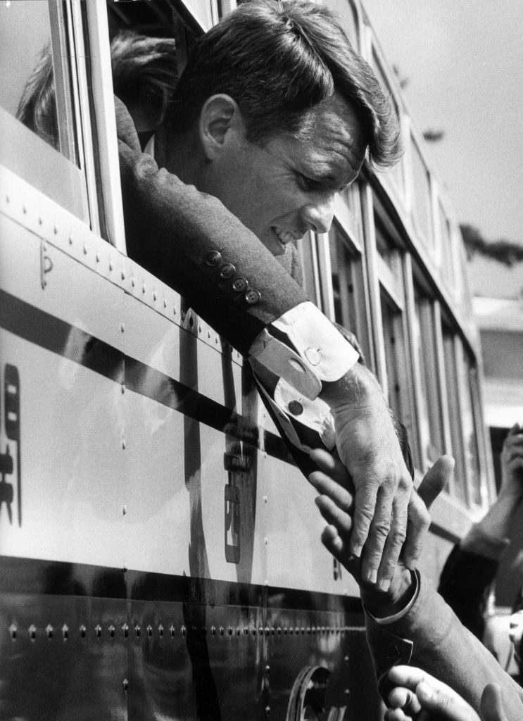 Robert Kennedy shakes hands from a train window, Japan, 1962.
