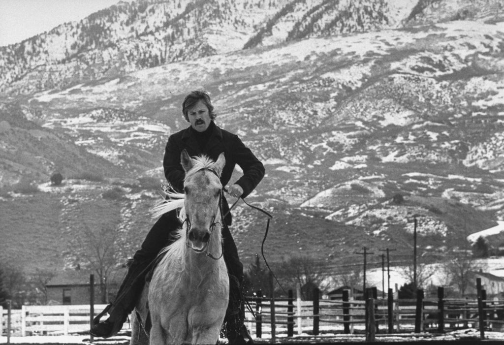Robert Redford exercises one of his eight saddle horses on his ranch in Utah, 1970.