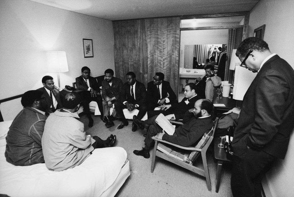 Stunned, silent members of the Southern Christian Leadership Conference in Dr. King's room at the Lorraine Motel, April 4, 1968, including Andrew Young (far left, under table lamp) and civil rights leader and Dr. King's colleague, Rev. Ralph Abernathy, in