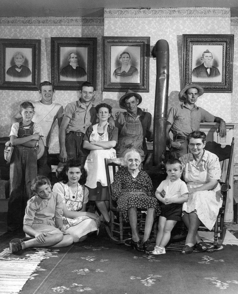 "Caption that accompanied this picture in the July 26, 1948, issue of LIFE: ""Four generations of the Russells gather for a portrait. The grandmother is 90, but she is still active. The portraits on wall at left are of old Mrs. Russell's parents, at right those at her late husband."""