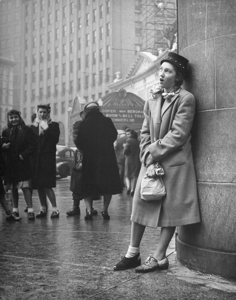 A teenager sings on a street corner as part of a sub-deb social club initiation in 1945.