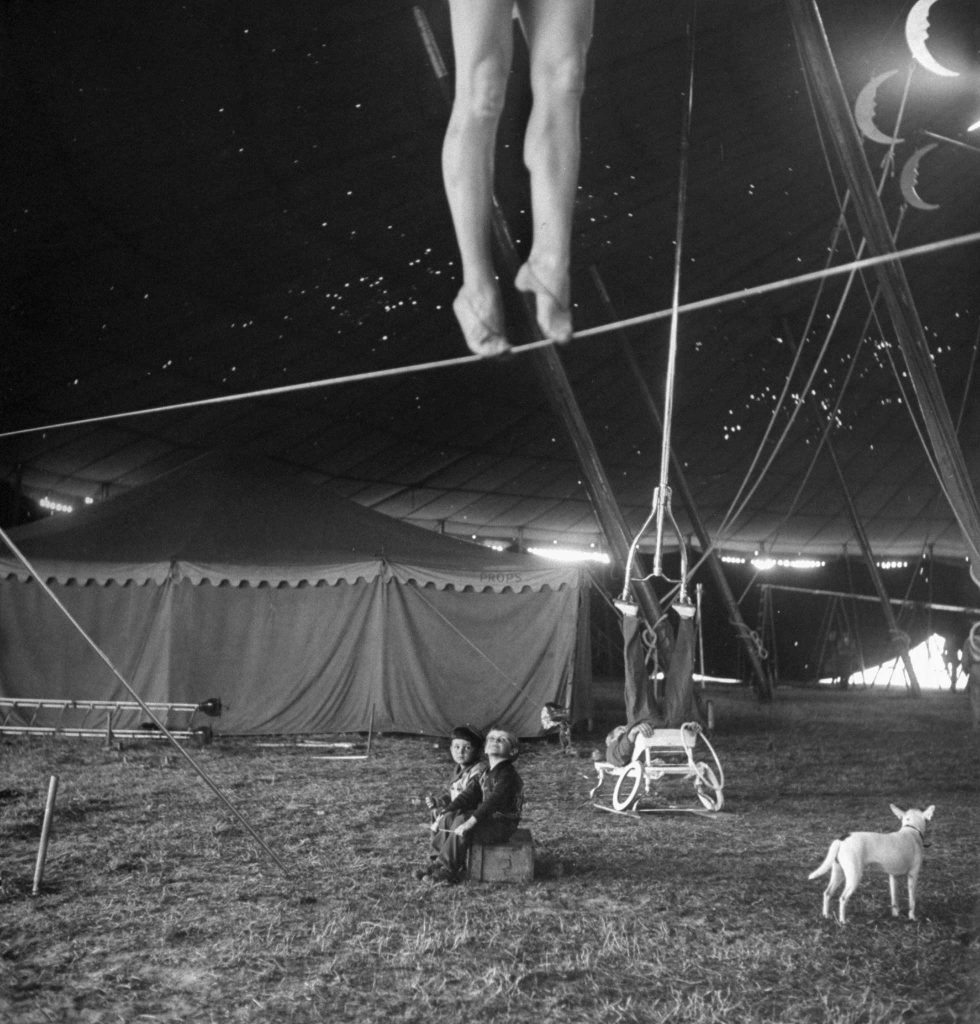 "From a story on the Ringling Bros. Circus in the April 4, 1949, issue of LIFE. The caption for this picture: ""Nothing but circus all day every day is the happy fate of these two performers' tots, who sit around the big tent watching as the pretty Miss Lola practices on a tightwire and an acrobat balances an odd contraption on his feet."""