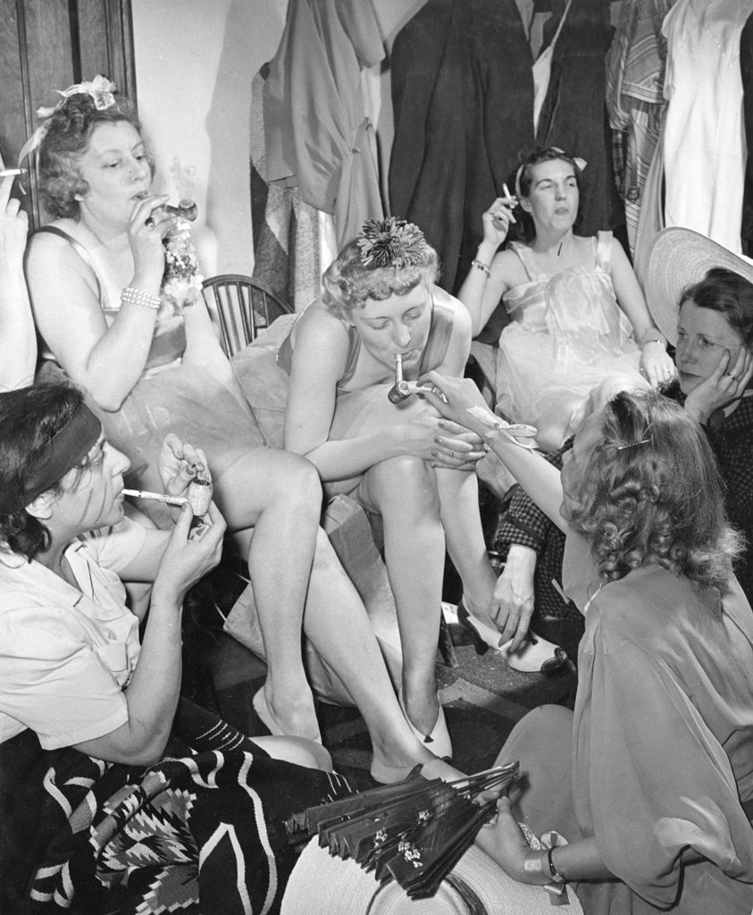 "Performers scheduled for later in the evening savor their corncob pipes in a dressing room. LIFE noted the corncobs would likely be a one-time enjoyment: ""It wouldn't do in Milford."""