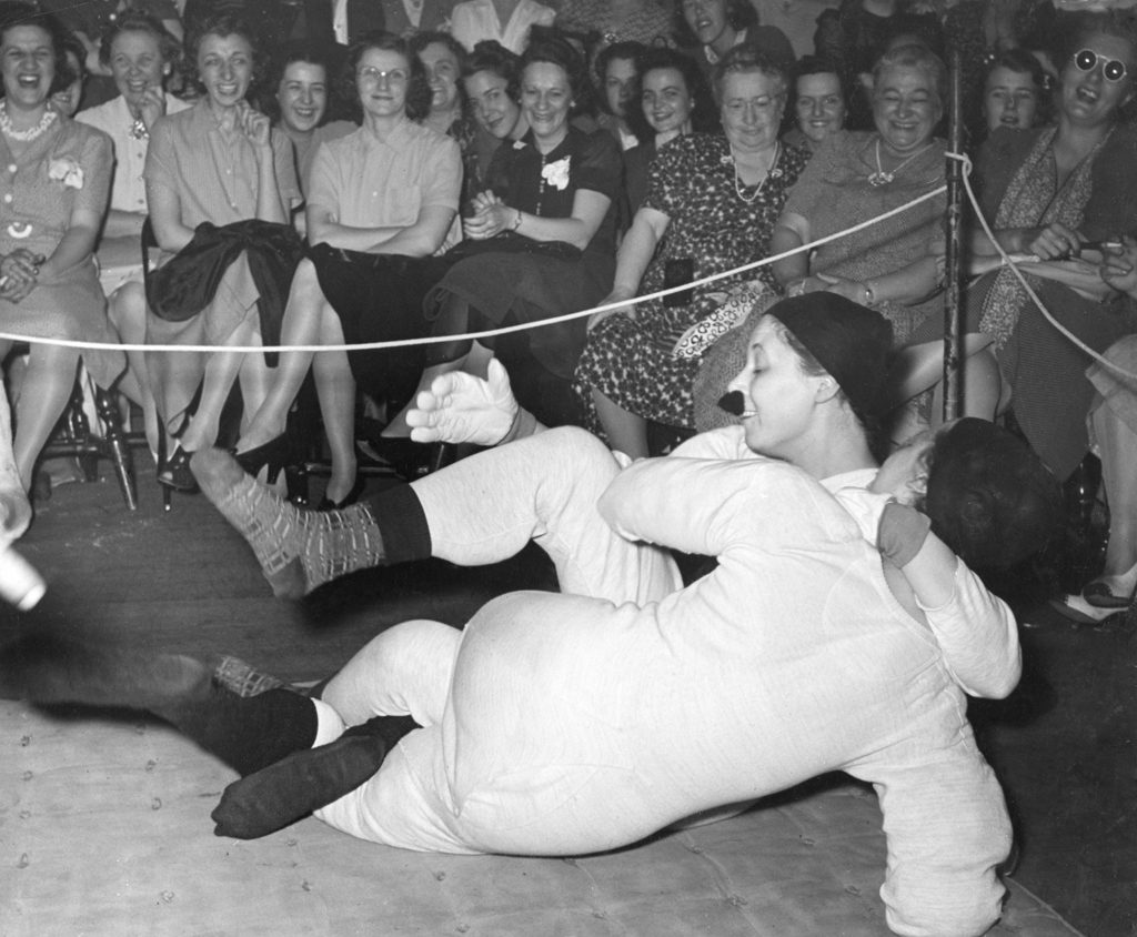 "LIFE on the battle: ""Huffing and puffing, they punish the mat."" Joan Thornwaite (back to camera) ""won by tickling in five minutes."" Note: Her opponent's mustache is attached to her face with chewing gum."