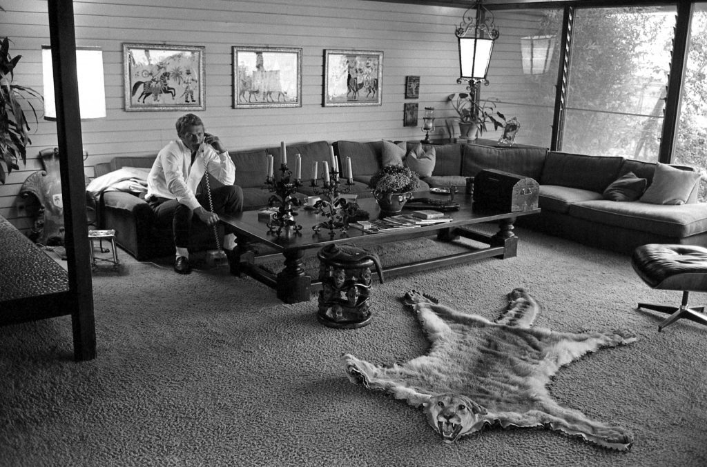 McQueen takes a call in the living room of his eclectic home in Hollywood, 1963.