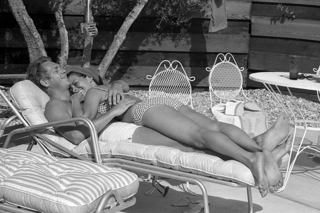 Steve McQueen and his wife Neile Adams lounge on the patio by the pool at their Palm Springs bungalow, 1963.
