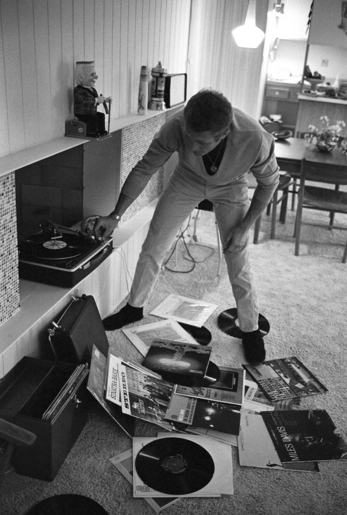 At his Palm Springs bungalow, Steve McQueen puts on a record, with LPs by Miles Davis, Sonny Rollins and Frank Sinatra scattered at his feet, 1963.