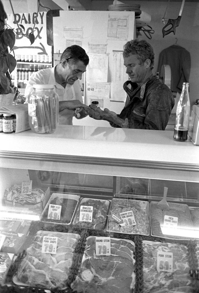 Steve McQueen makes a stop at a grocery store in Pearblossom, Calif., to get some treatment for race-bloodied hands, 1963.