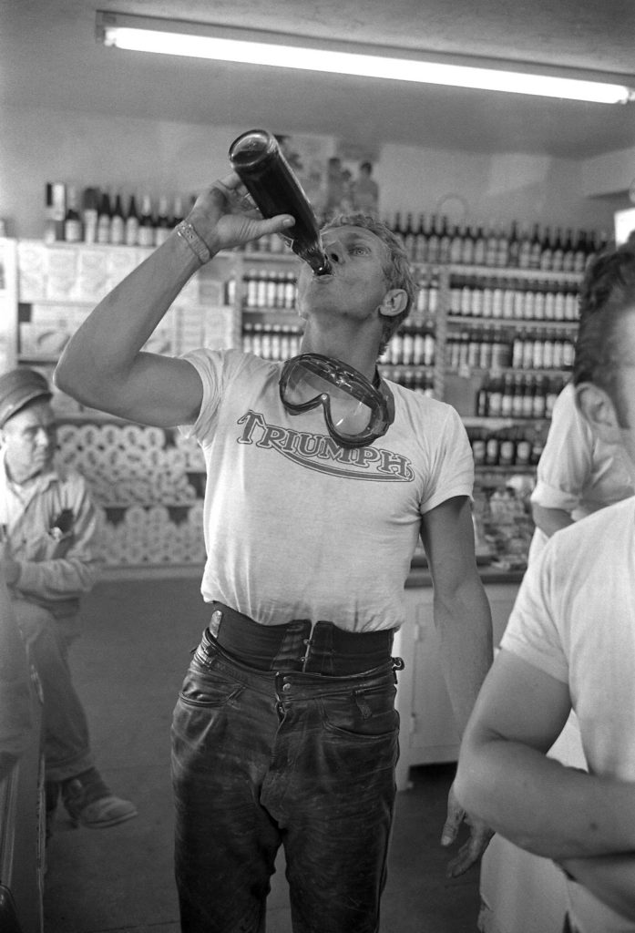McQueen takes a deep swig of a tall, cool drink, 1963.