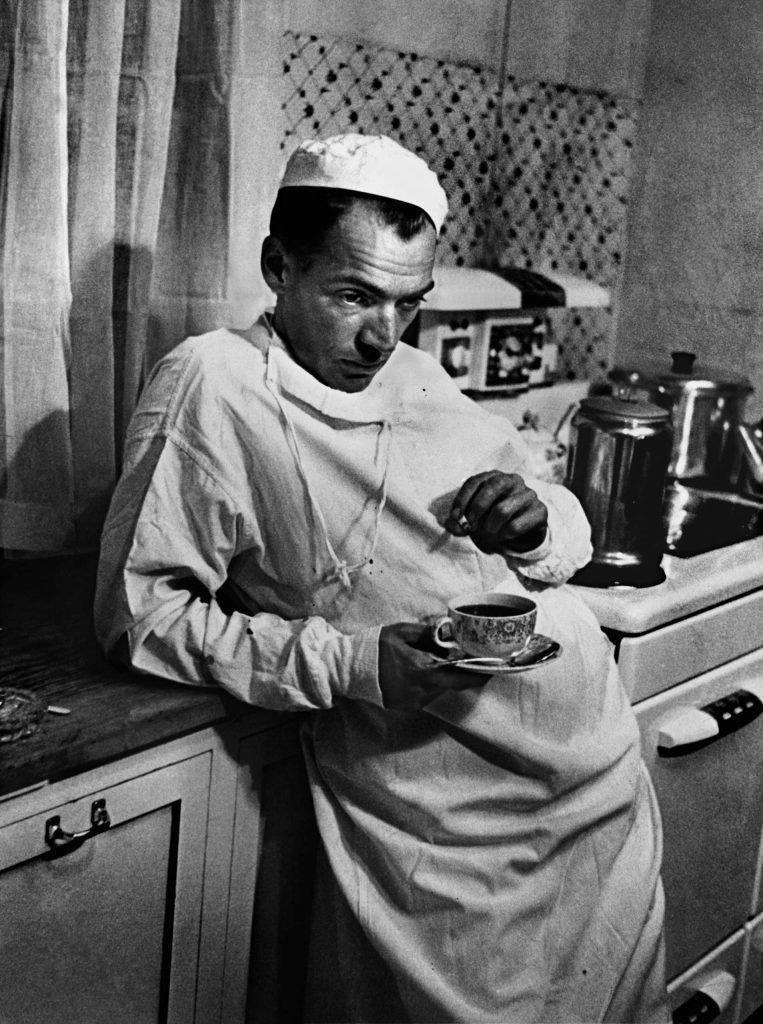 "Dr. Ernest Ceriani, a general practitioner in tiny Kremmling, Colorado, stands in the town's hospital kitchen after a surgery that lasted until 2 AM. This was the final image in W. Eugene Smith's groundbreaking photo essay, ""Country Doctor,"" originally published in the September 20, 1948, issue of LIFE."