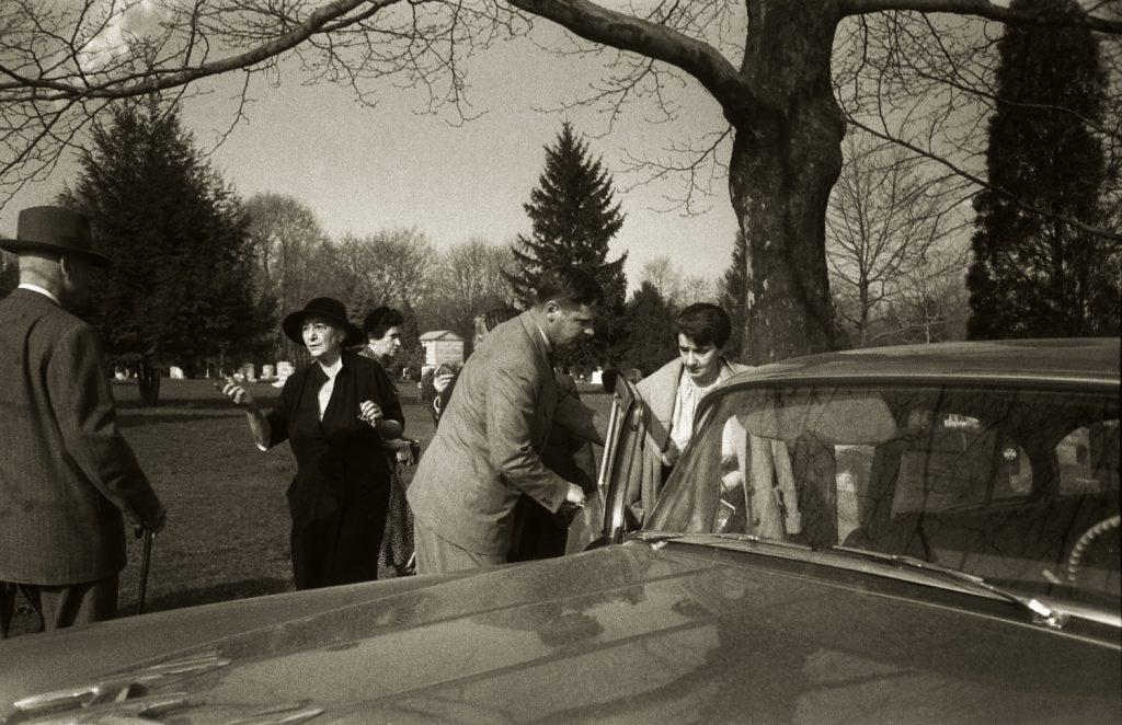 An unidentified man holds a car door open for Albert Einstein's secretary, Helen Dukas, following Einstein's cremation, April 1955.